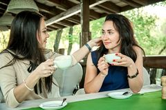 Two young romantic girls flirting. And drinking coffee in a restaurant in the outdoors Royalty Free Stock Photos