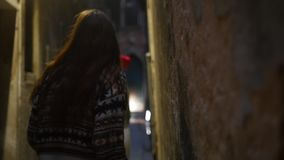 Two young scared women walking on the narrow mysterious street and looking around