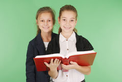 Two young school girls with red book. Isolated on green Stock Photo