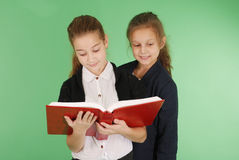 Two young school girls with red book. Isolated on green Stock Image