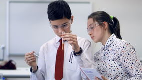 Two young school students working on a science project together in chemistry classroom. stock video footage