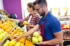 Two young sellers selecting fresh fruit and preparing for working day in fruitshop. Shot of two young sellers selecting fresh fruit and preparing for working stock image