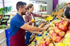 Two young sellers selecting fresh fruit and preparing for working day in fruitshop. Shot of two young sellers selecting fresh fruit and preparing for working royalty free stock photography