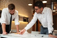 Two young serious businessmen working on a business plan. While standing over desk with graph indoors Stock Photo
