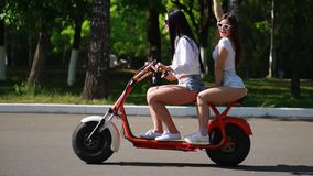 Two young and brunette friends with loose hair in short denim shorts riding an electric motorcycle in the Park on a