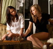 Two young and girls are playing chess Stock Photos