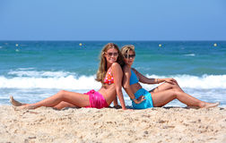 Two young and healthy girls sitting on a sunny beach Stock Photos