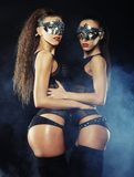 Two young sexy striptease dancer with mask Royalty Free Stock Photography