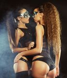 Two young sexy striptease dancer with mask Stock Photo