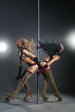 Two young sexy women exercise pole dance Royalty Free Stock Photography