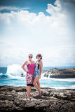Two young and sexy women on the rocks near the wild ocean. Storm, huge waves coming and splashing. Tropical island Nusa. Lembongan. The name of the place is Stock Image