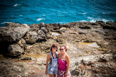 Two young and sexy women on the rocks near the wild ocean. Storm, huge waves coming and splashing. Tropical island Nusa. Lembongan. The name of the place is Royalty Free Stock Photo