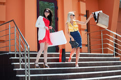 Two young fashion women with shopping bags on the mall steps Royalty Free Stock Photography