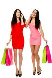 Two young shopping merry women talking by phone Royalty Free Stock Photo