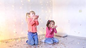 Two young sisters of European appearance sit on floor and throw up festive confetti. Two beautiful girls from European family sitting on floor in living room stock footage