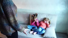 Two girls sit on couch and listen to mom`s remarks about bad behavior.