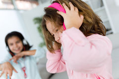 Two young sisters listening to music and dancing at home. Stock Images