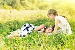 Two young sisters on nature. Older one is resting on younger one knees. Royalty Free Stock Photography