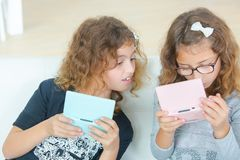 Two young sisters playing video gales. Adult royalty free stock photo
