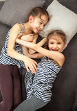 Two young sisters pushing each other on bed Royalty Free Stock Images