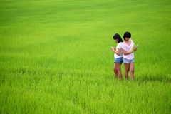 Two young sisters reading a book in paddy field Stock Photo