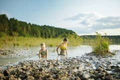 Two young sisters taking healing mud baths on lake Gela near Vilnius, Lithuania. Children having fun with mud. Kids playing with medicinal clay royalty free stock photo