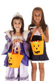 Two young sisters trick or treating a princess and a cheerleader. Halloween sisters princess cheerleader trick or treating stock photography