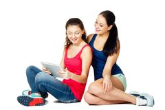 Two young sitting women looking in pad Stock Photography