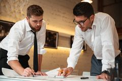 Two young smart businessmen working on a business plan Royalty Free Stock Photos