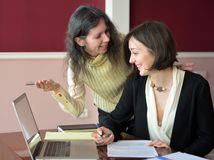 Two young smartly dressed women filling out forms at a vintage office desk in front of a laptop. Young smartly dressed lady discusses issues with another young stock image