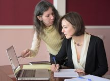 Two young smartly dressed women filling out forms at a vintage office desk in front of a laptop royalty free stock images