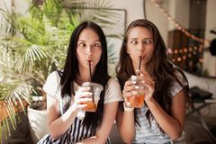 Two young smiling beautiful slim girls with long dark hair,wearing casual clothes, sit next to each other and look at royalty free stock images