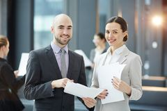 Brokers with papers. Two young smiling brokers with contracts looking at camera during negotiation Stock Images