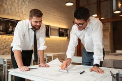 Two young smiling businessmen working on a business plan. While standing over desk with graph indoors Stock Photography