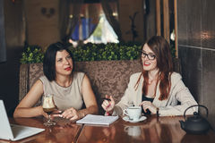 Two young smiling caucasian businesswomen with laptop. Women in cafe Royalty Free Stock Image