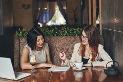 Two young smiling caucasian businesswomen with laptop. Women in cafe Royalty Free Stock Images