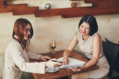 Two young smiling caucasian businesswomen with notebook. Women in cafe Stock Photos