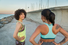 Two young smiling fitness women talking Stock Images