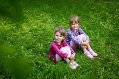Two young smiling girls in the grass Royalty Free Stock Image