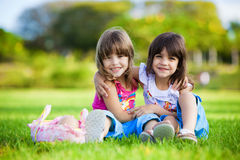 Two young smiling girls hugging in the grass Stock Image