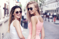 Two young smiling girls walking in the city. Royalty Free Stock Images