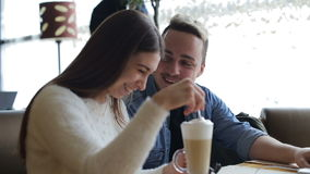 Two young, smiling and happy people have a chat in the cafe stock footage