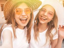 Two beautiful trendy girls posing in the street. Two young smiling hipster blond women in summer white t-shirt clothes. Girls taking selfie self portrait photos royalty free stock photography