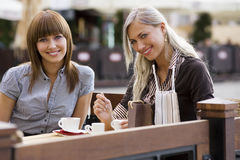 Two young smiling lady in cafe Stock Image