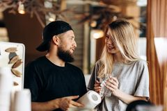 Two young smiling people,a blonde girl and man with beard.dressed in casual outfit, stand next to each other and look at royalty free stock photo