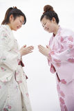 Two young smiling  woman in Japanese kimonos bowing to each other, studio shot Royalty Free Stock Photography
