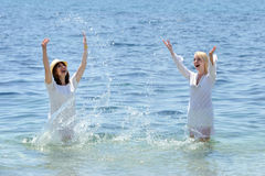 Two young smiling womans splashing water in sea Royalty Free Stock Images