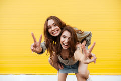 Two young smiling women friends standing over yellow wall. Picture of two young smiling women friends standing over yellow wall. Looking at camera showing peace Royalty Free Stock Photo