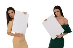 Two young smiling women holding two pieces of blank paper stock photo