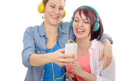 Two young smiling women taking a selfie. Two young smiling women taking a selfie on white background Stock Images